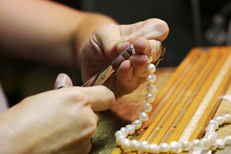 Jeweler threading a pearl necklace